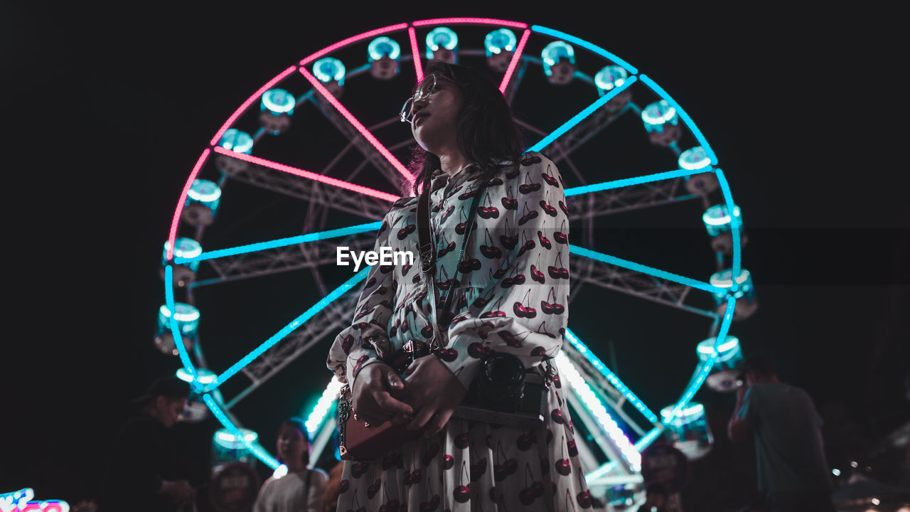 Low angle view of woman standing against ferris wheel at night