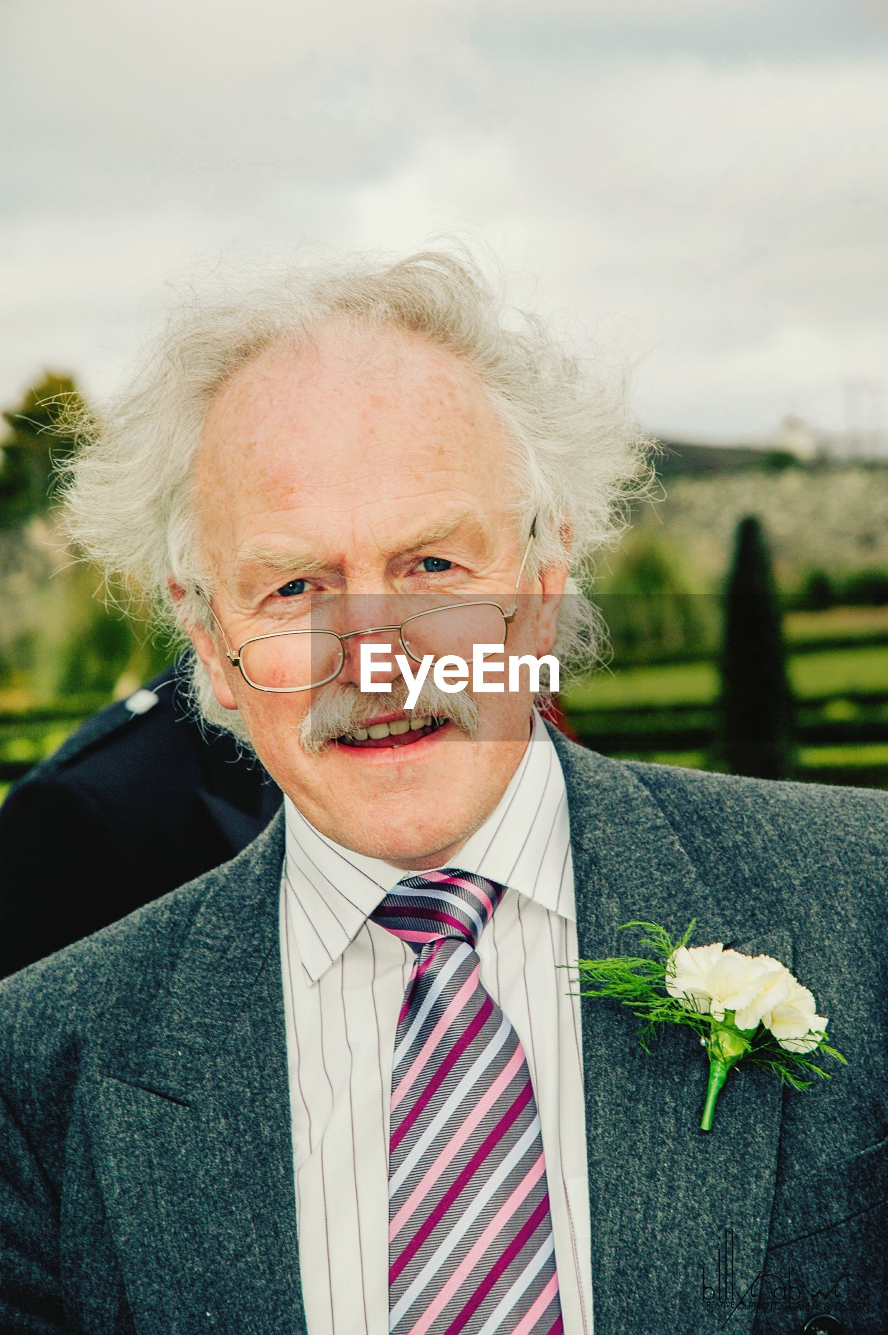 Portrait of senior man wearing boutonniere against sky