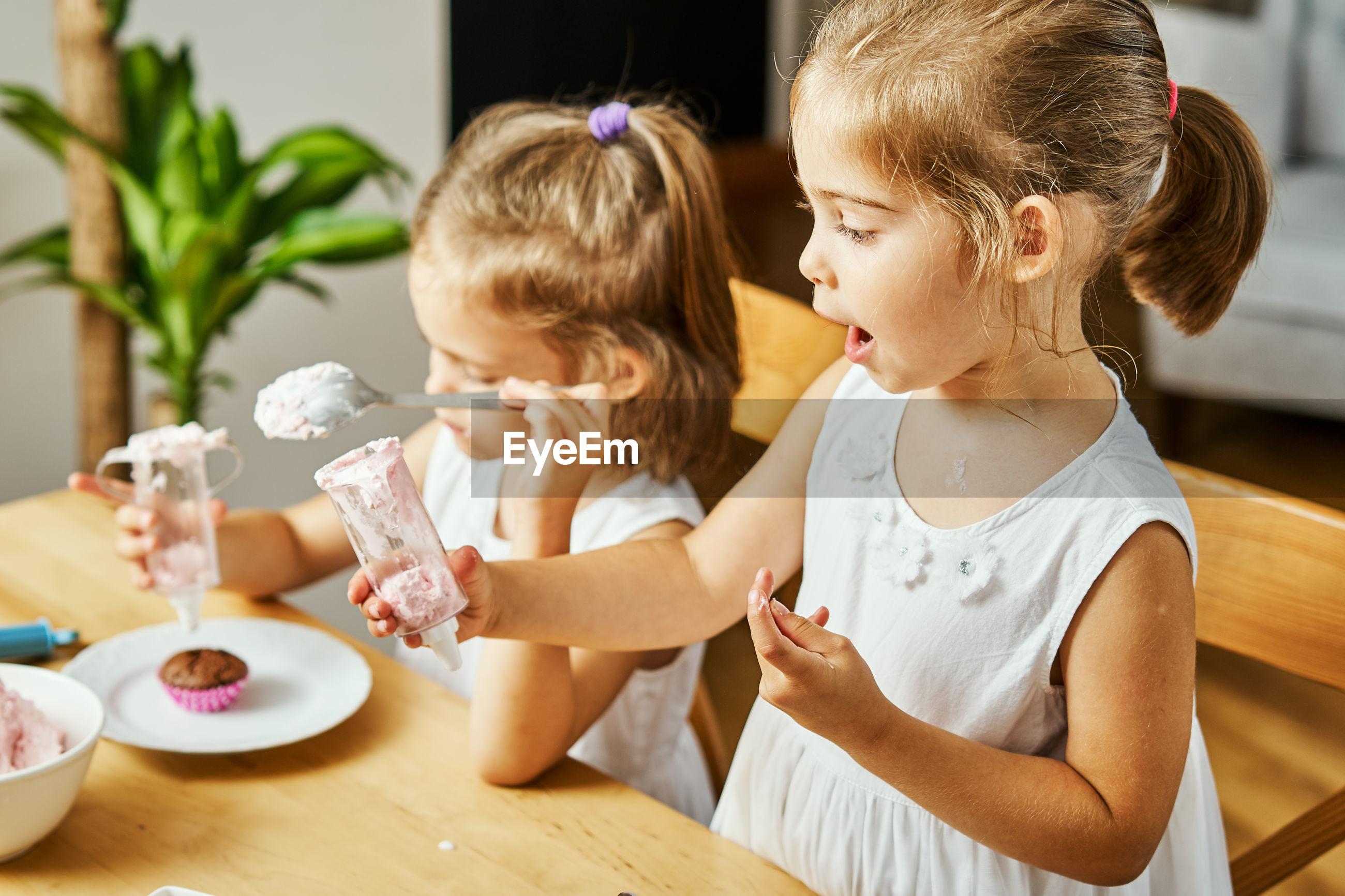 Siblings preparing food on table