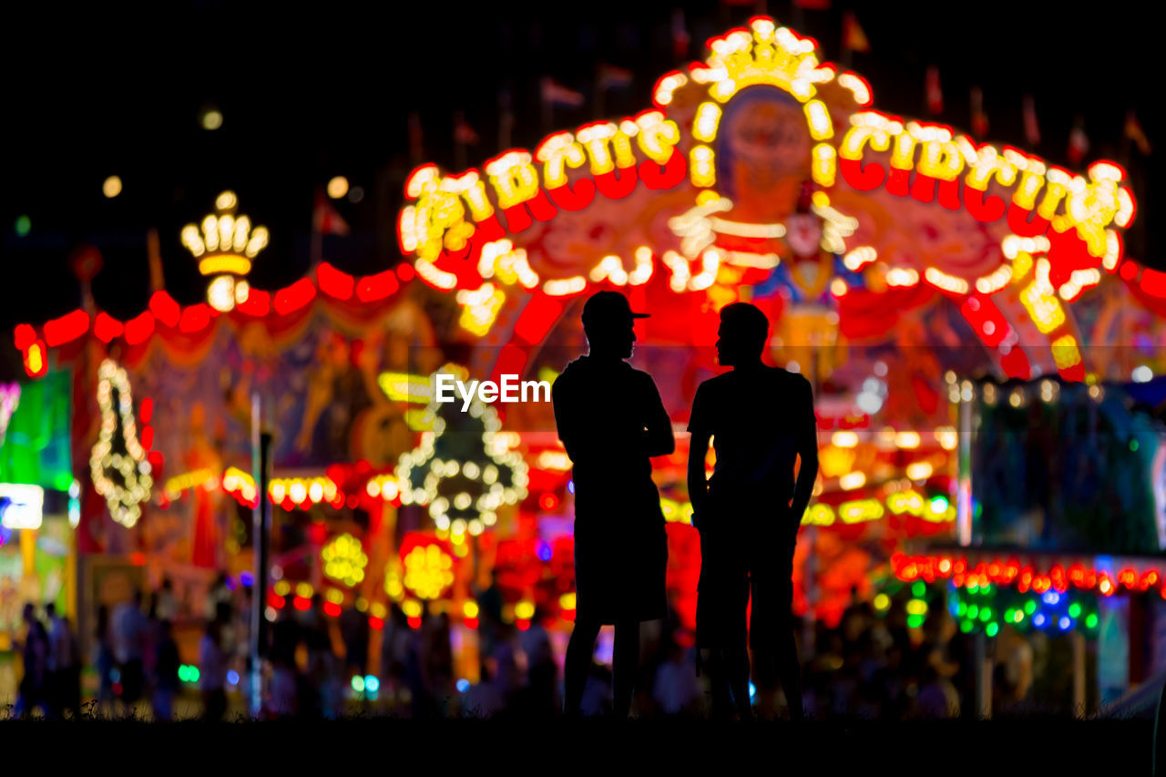 illuminated, night, lighting equipment, two people, glowing, men, real people, celebration, decoration, focus on foreground, outdoors, standing, people, togetherness, representation, lifestyles, retail, leisure activity, text
