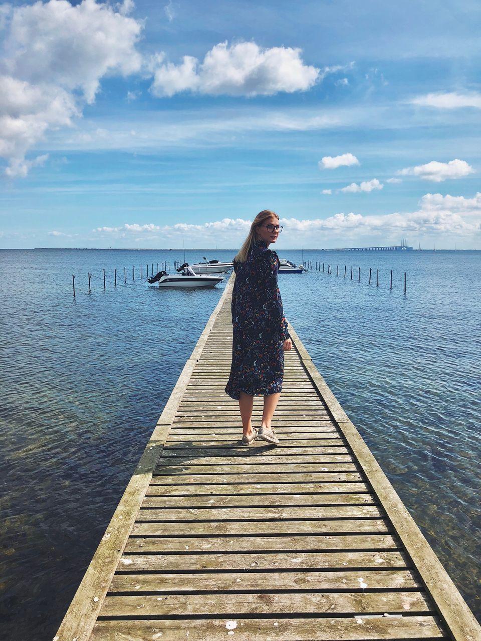 Full length of woman walking on pier over lake against sky