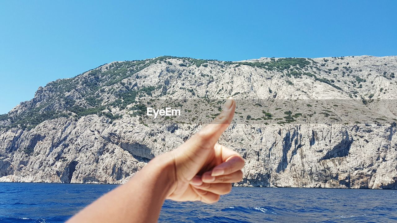 Cropped hand of person showing thumbs up against rocky mountains