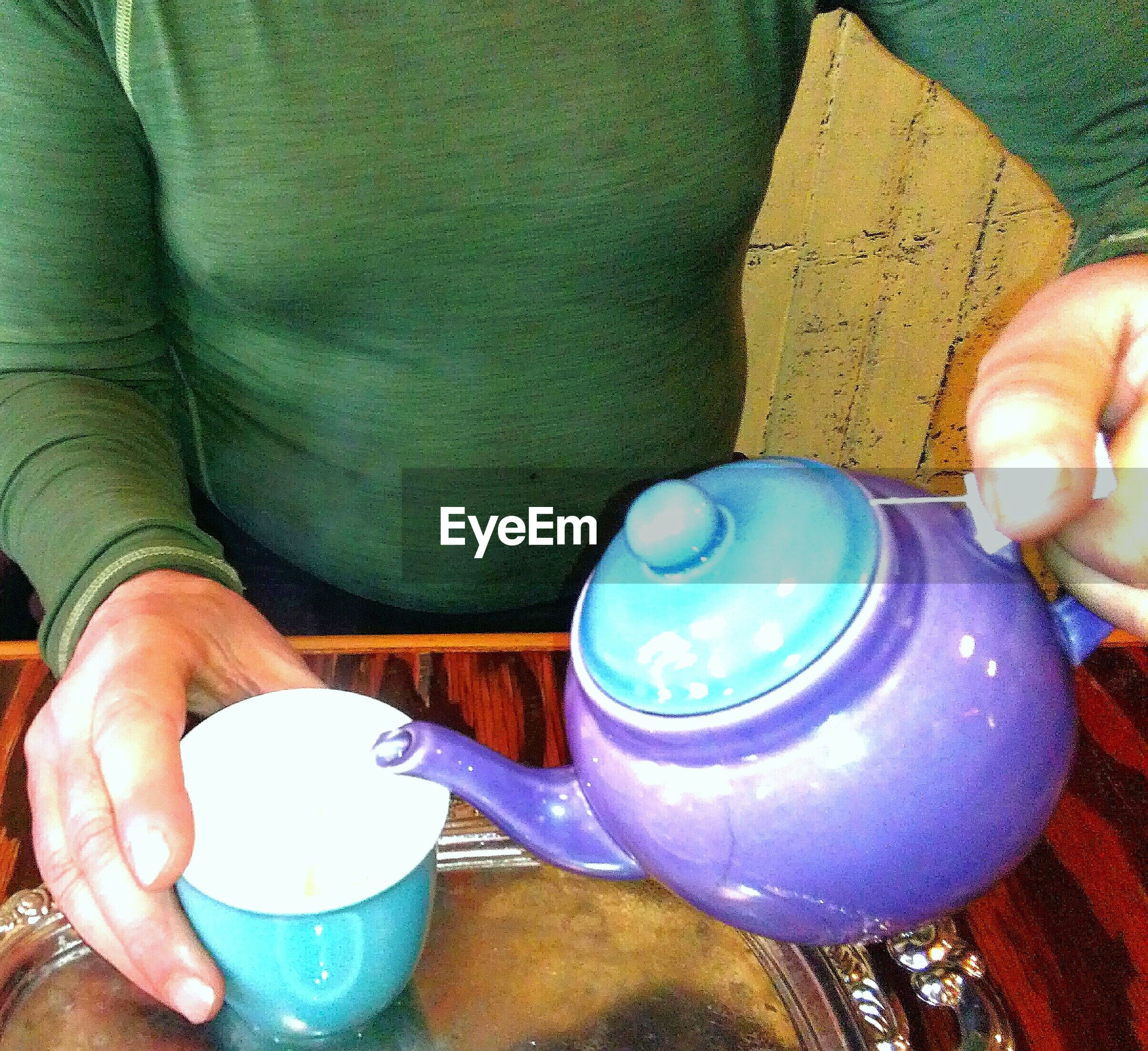 Midsection of person pouring water into cup
