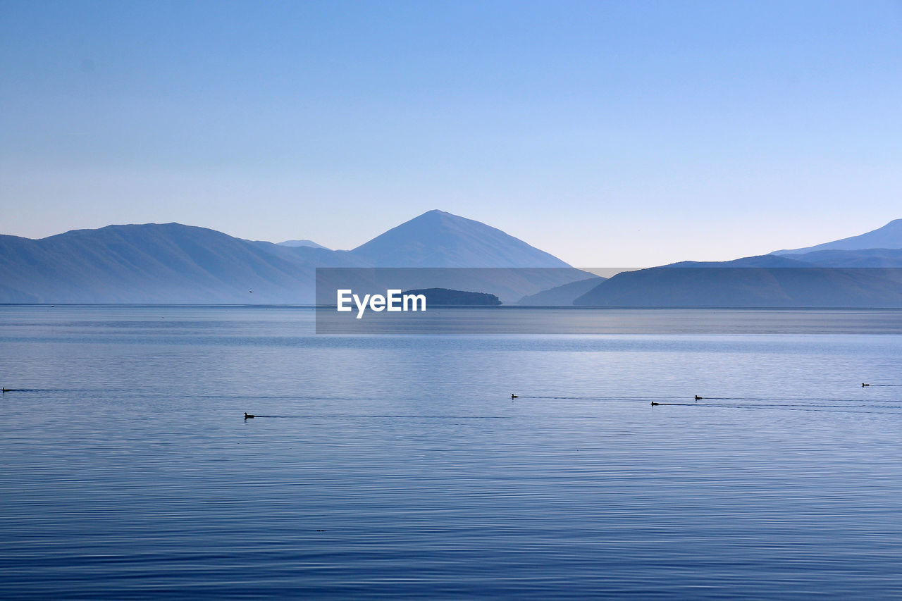 tranquil scene, mountain, tranquility, scenics, beauty in nature, nature, blue, no people, copy space, water, outdoors, clear sky, waterfront, lake, mountain range, day, sky