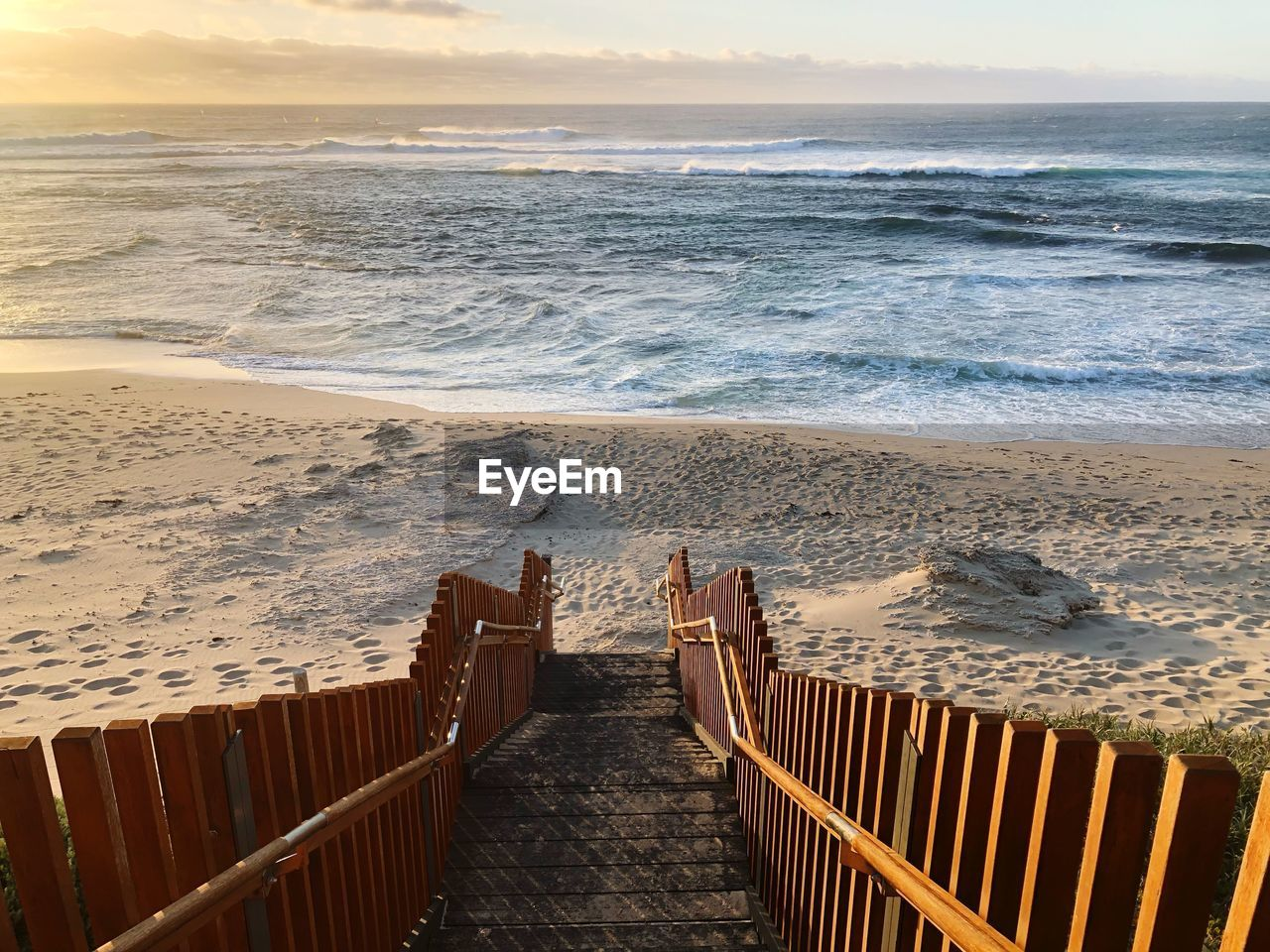 sea, beach, water, land, sky, beauty in nature, horizon, horizon over water, wave, scenics - nature, motion, nature, sand, sunset, railing, idyllic, tranquil scene, aquatic sport, surfing, outdoors