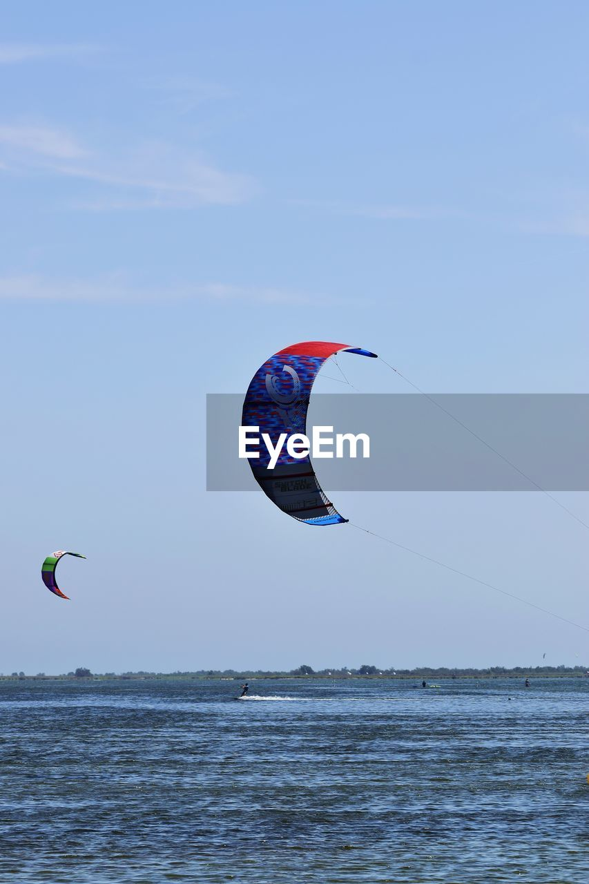 extreme sports, adventure, sea, leisure activity, real people, nature, sport, horizon over water, parachute, water, lifestyles, kiteboarding, exhilaration, mid-air, beauty in nature, vitality, weekend activities, scenics, outdoors, sky, paragliding, day, vacations, waterfront, flying, men, people