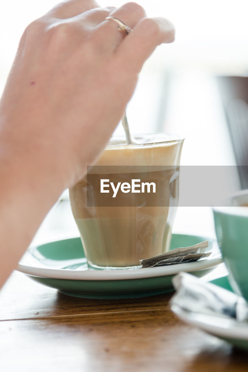 drink, refreshment, food and drink, human hand, hand, human body part, table, one person, coffee, real people, glass, selective focus, indoors, coffee - drink, saucer, cup, mug, freshness, coffee cup, drinking glass, hot drink, crockery, latte, finger