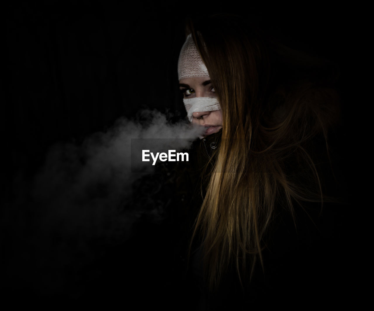 Portrait of woman with bandages on face smoking against black background
