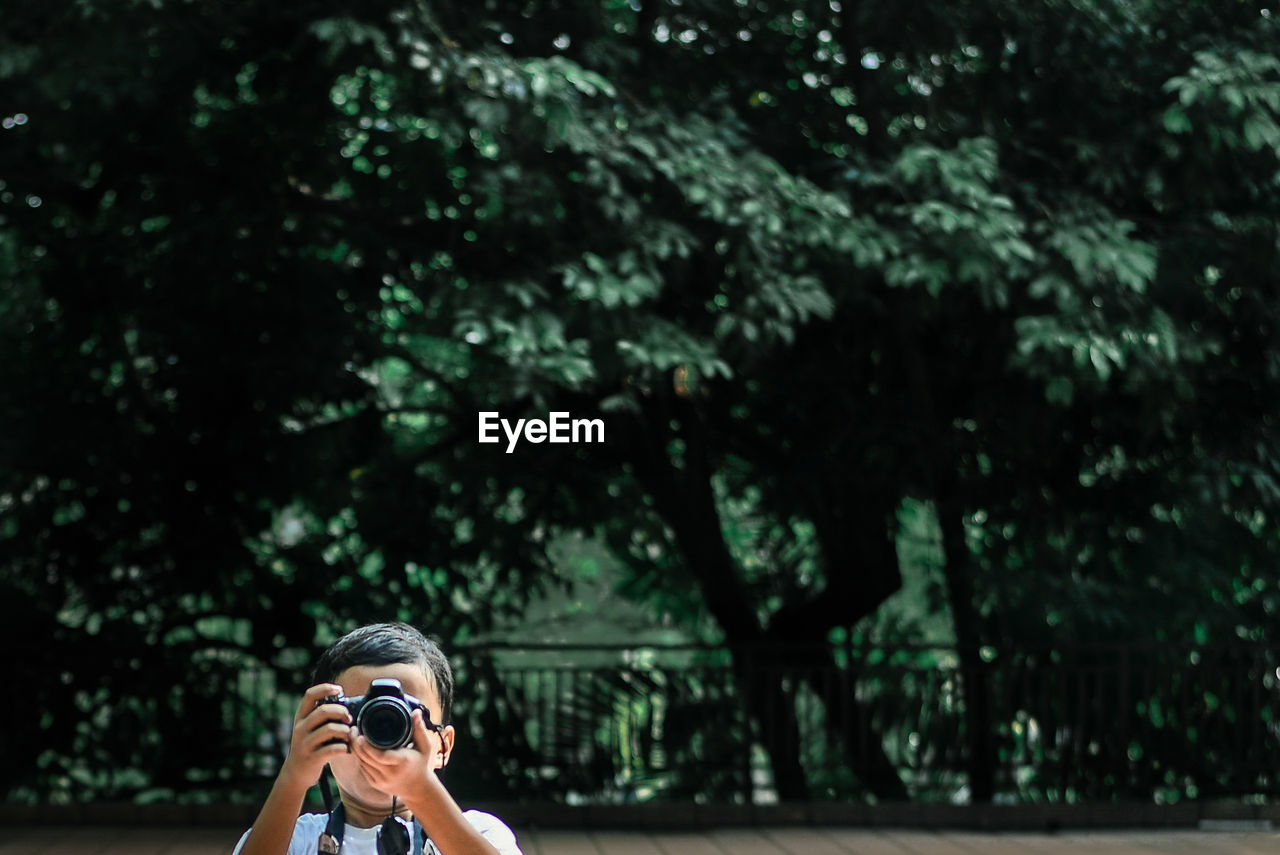 Young Boy Photographing In A Park