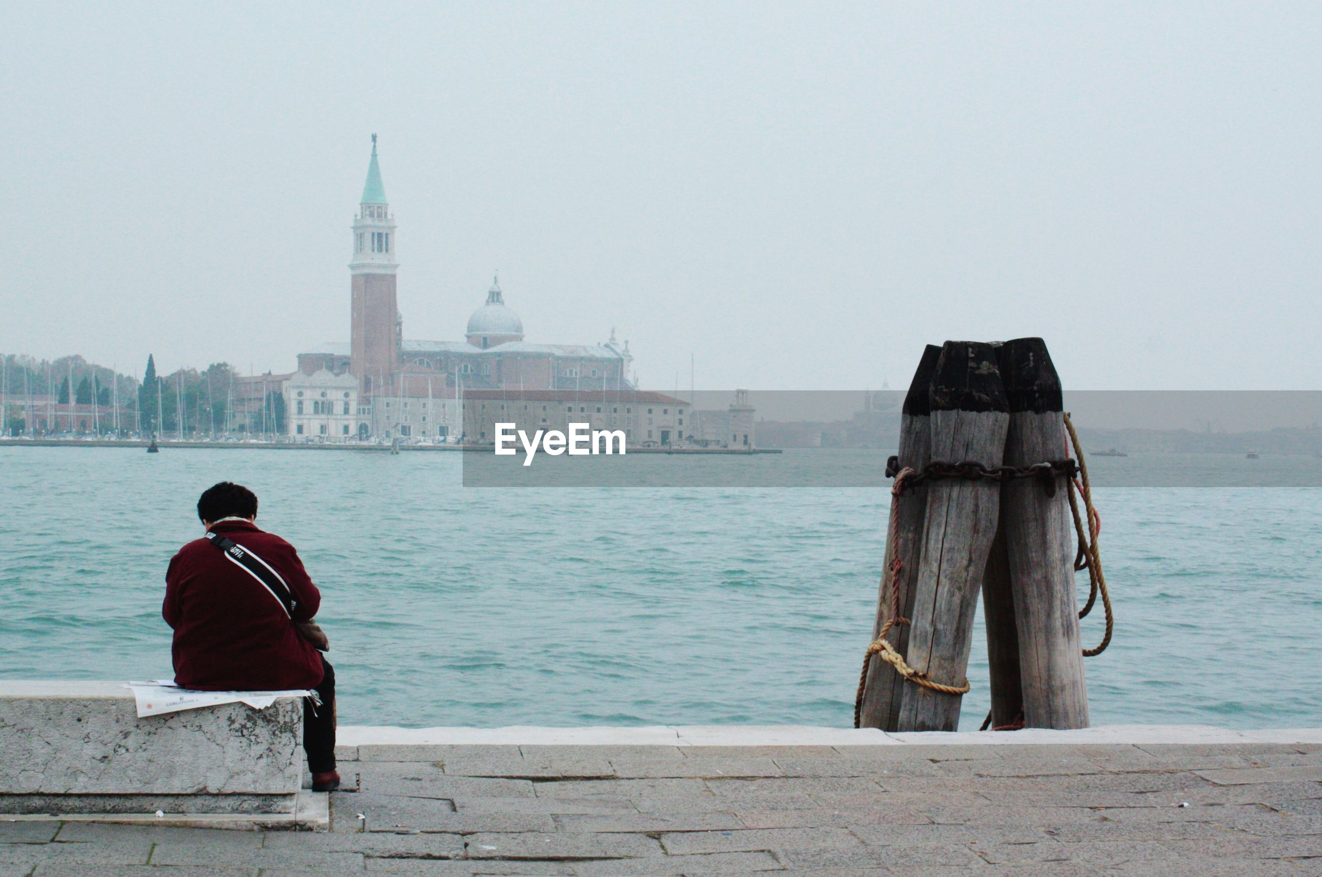 Man sitting by grand canal against church of san giorgio maggiore