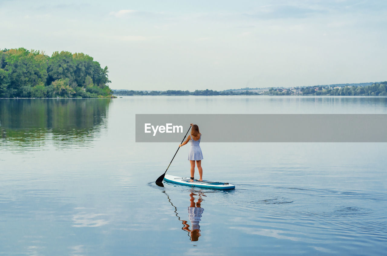 Woman on boat in lake against sky