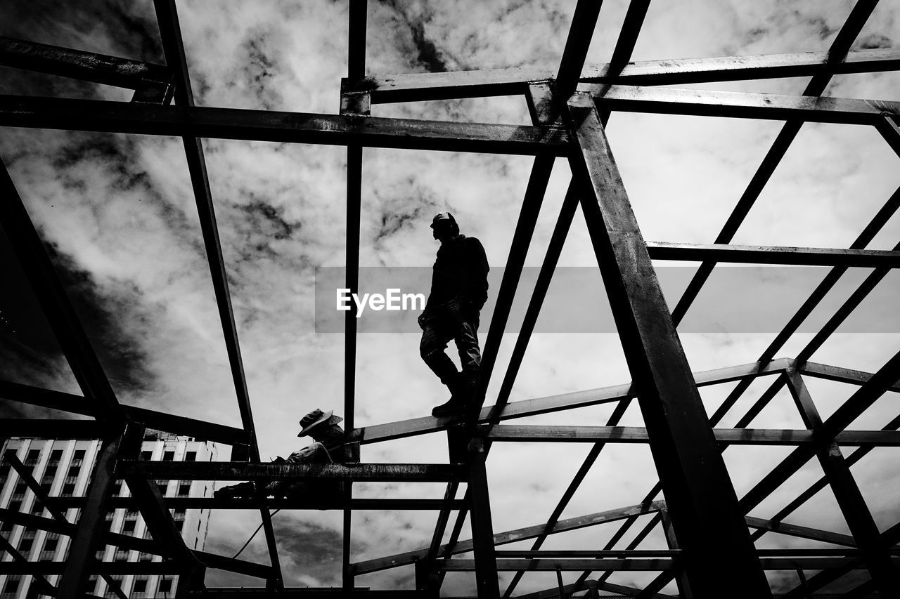 construction site, silhouette, low angle view, occupation, real people, construction worker, working, architecture, risk, sky, built structure, men, one person, day, manual worker, outdoors, window washer, hardhat, people