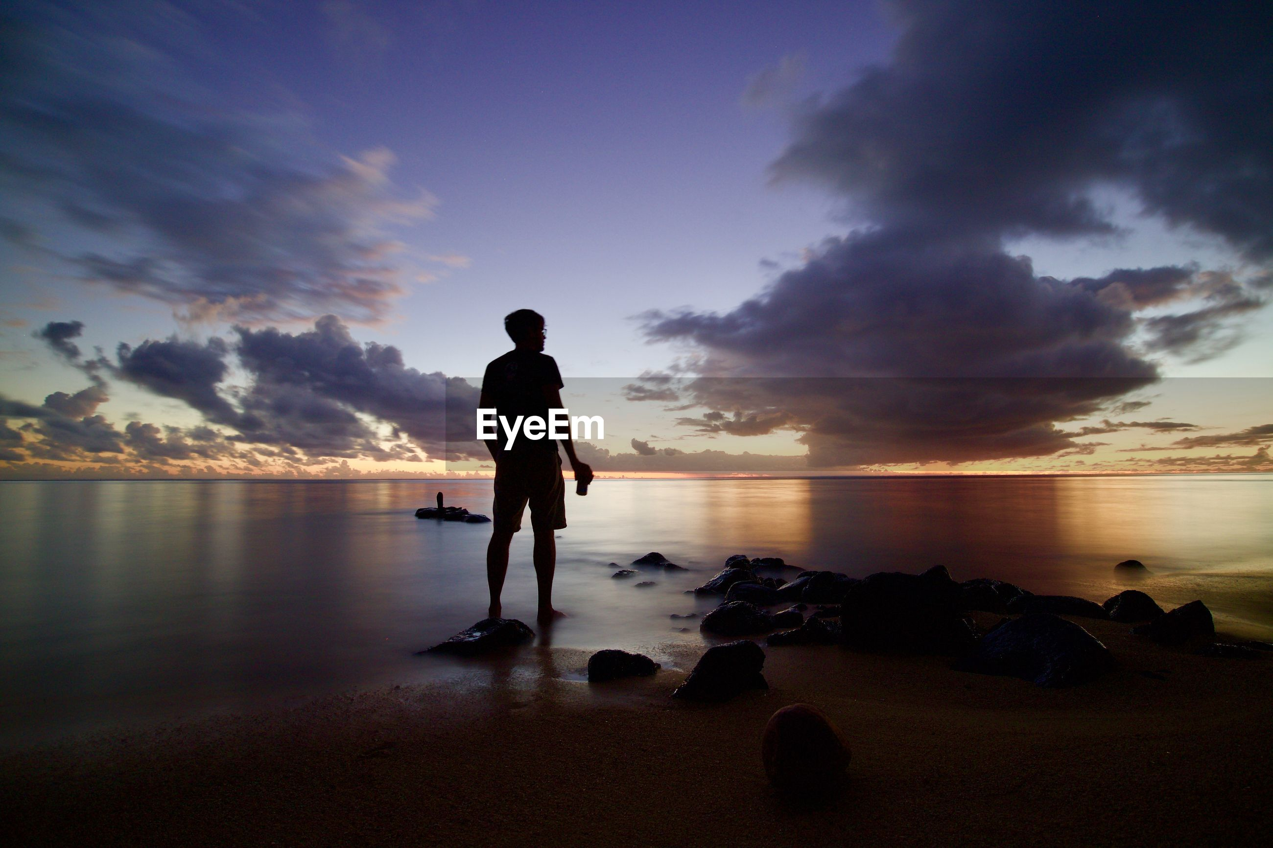 Full length of man standing on rock at beach against sky during sunset