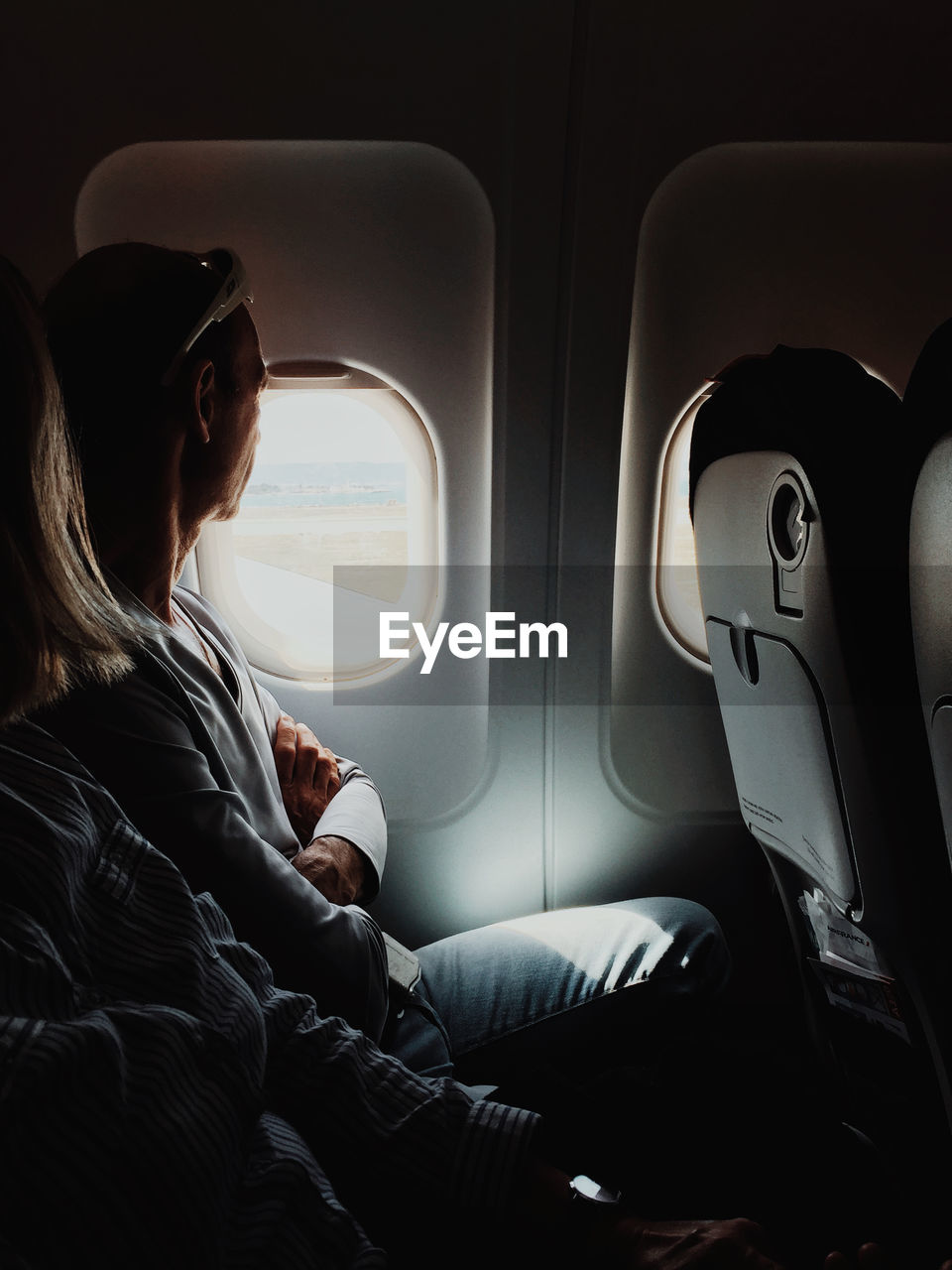 mode of transportation, vehicle interior, transportation, air vehicle, sitting, airplane, real people, travel, window, vehicle seat, women, seat, journey, casual clothing, public transportation, adult, one person, lifestyles, leisure activity, three quarter length, hairstyle, outdoors, airplane seat