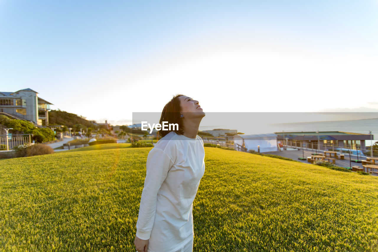 Woman standing on grass against clear sky