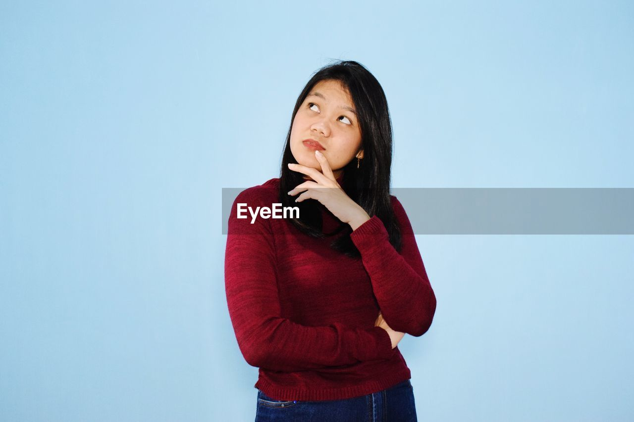BEAUTIFUL YOUNG WOMAN LOOKING AWAY AGAINST BLUE BACKGROUND