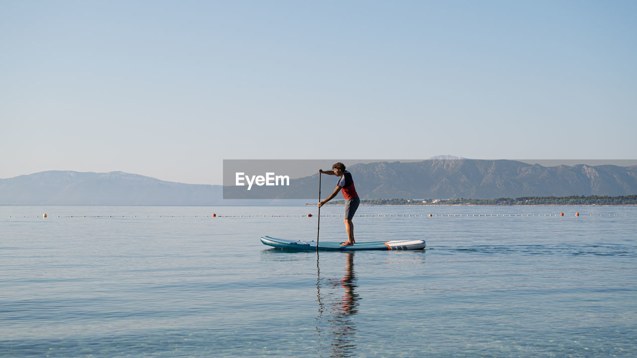 Man standing on paddleboard in sea against clear sky