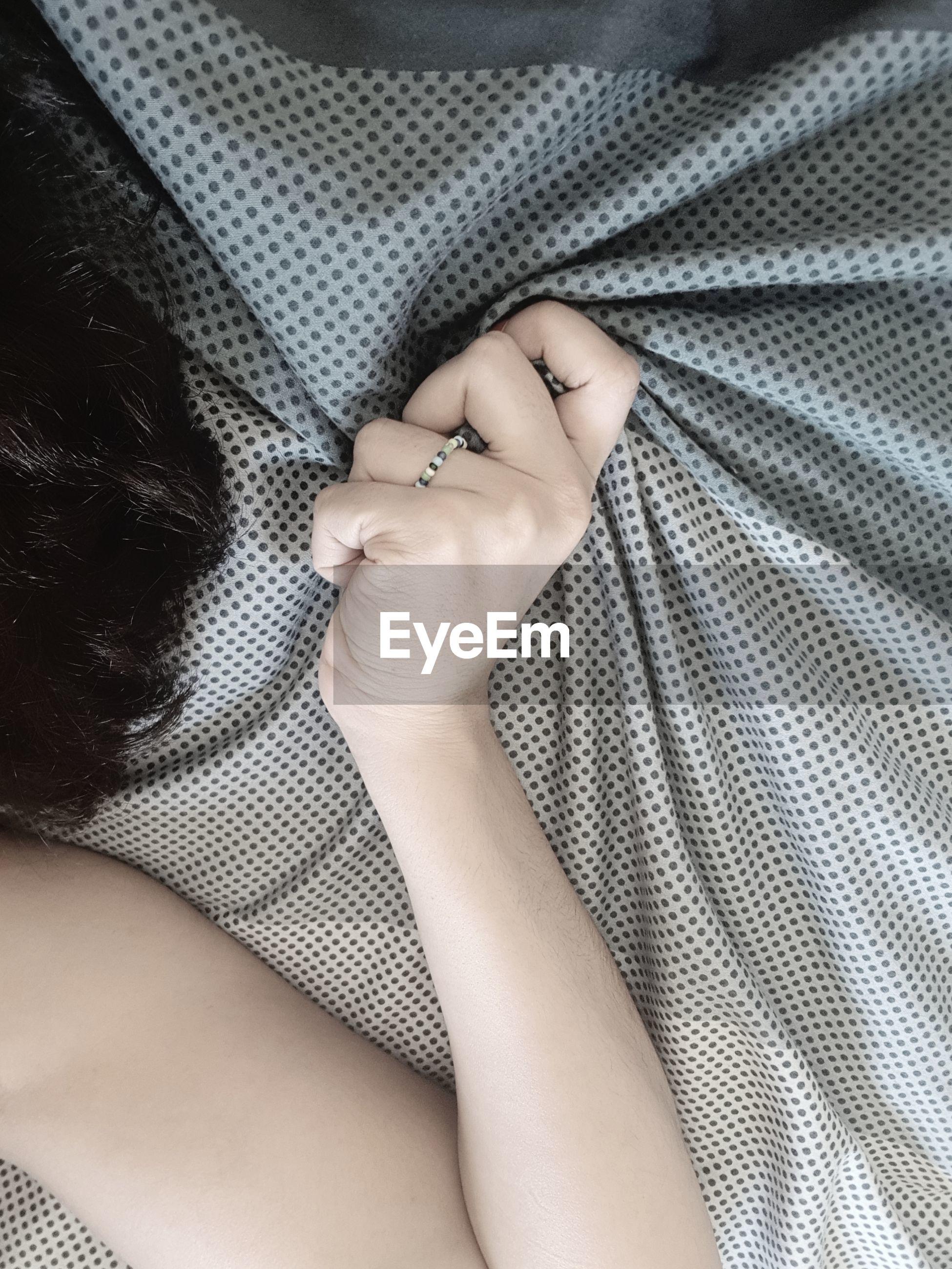 Cropped hand of woman crumpling sheet