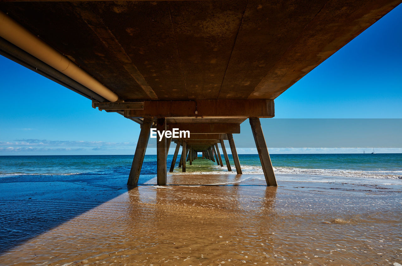 water, sea, beach, land, sky, horizon over water, built structure, pier, architecture, no people, scenics - nature, nature, horizon, underneath, beauty in nature, below, architectural column, blue, connection, outdoors