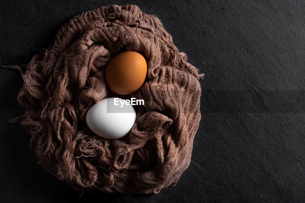 High angle view of eggs on scarf over table