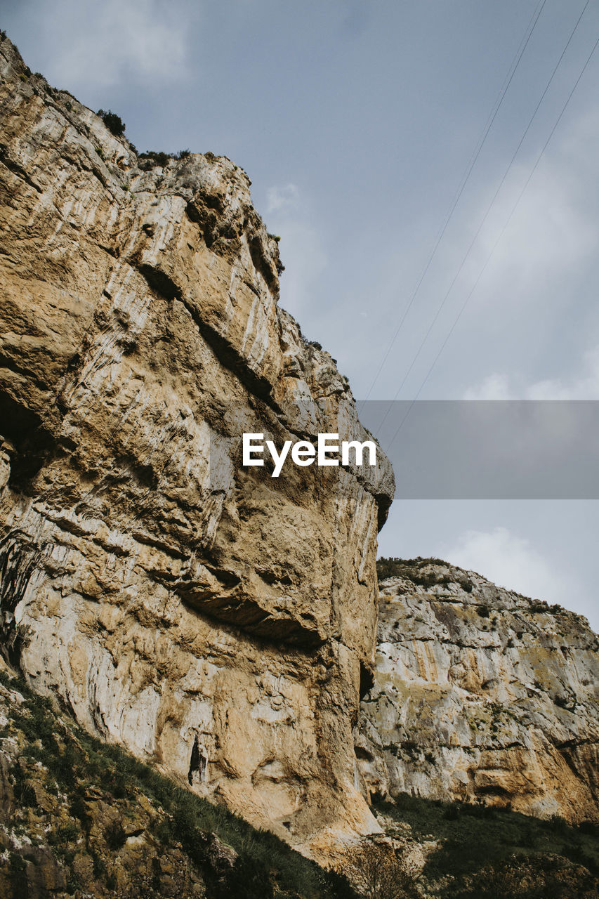 low angle view, sky, rock, rock - object, rock formation, solid, nature, day, mountain, no people, cliff, geology, outdoors, tranquility, physical geography, cloud - sky, beauty in nature, cable, rocky mountains, formation, eroded, mountain peak