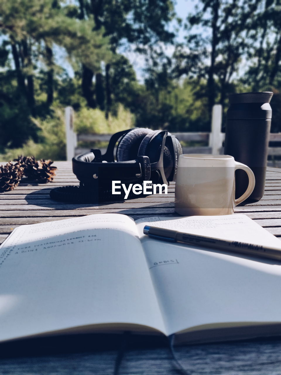 CLOSE-UP OF COFFEE CUP ON TABLE AGAINST TREES