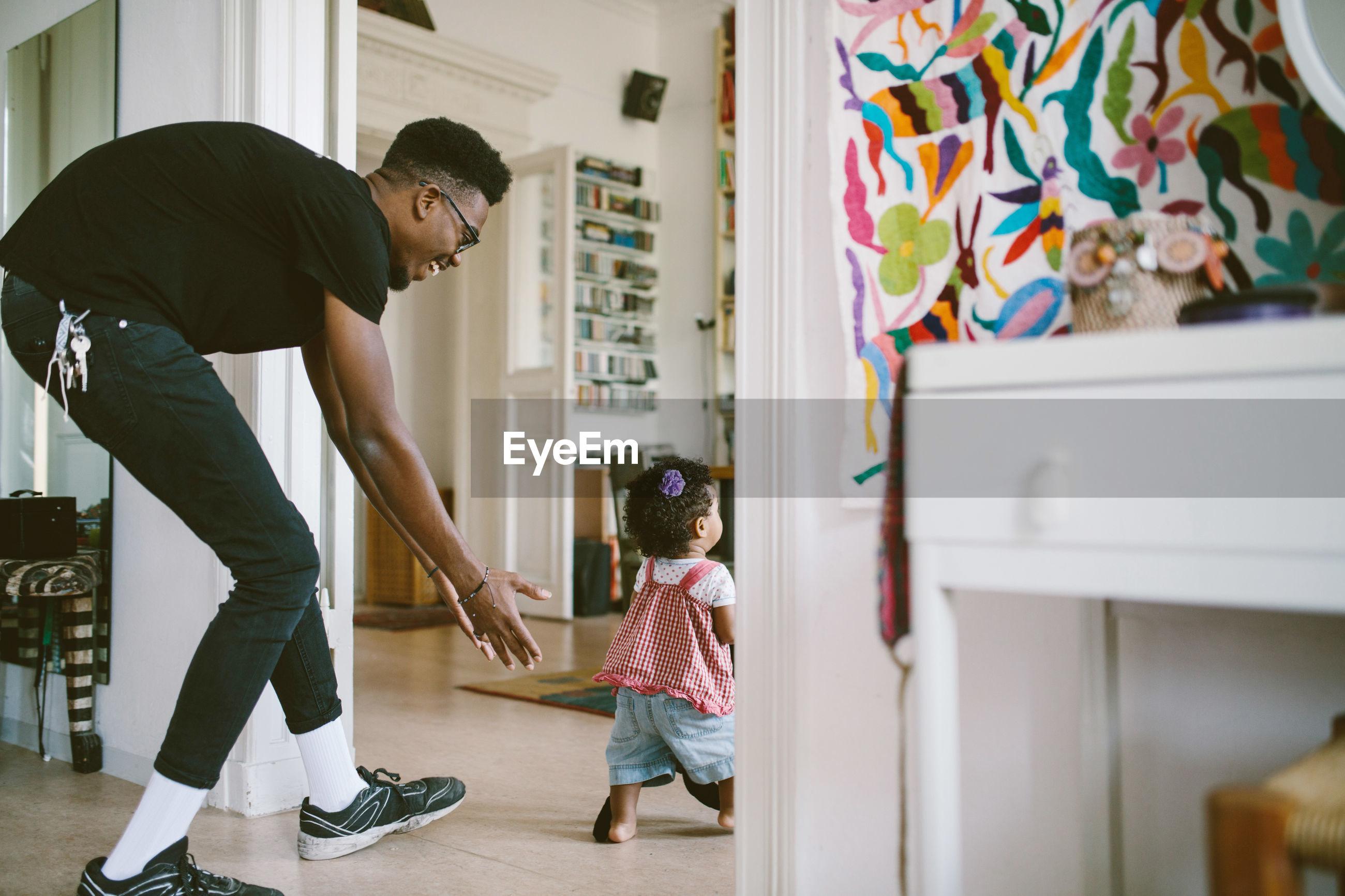 Smiling young man walking behind daughter at home