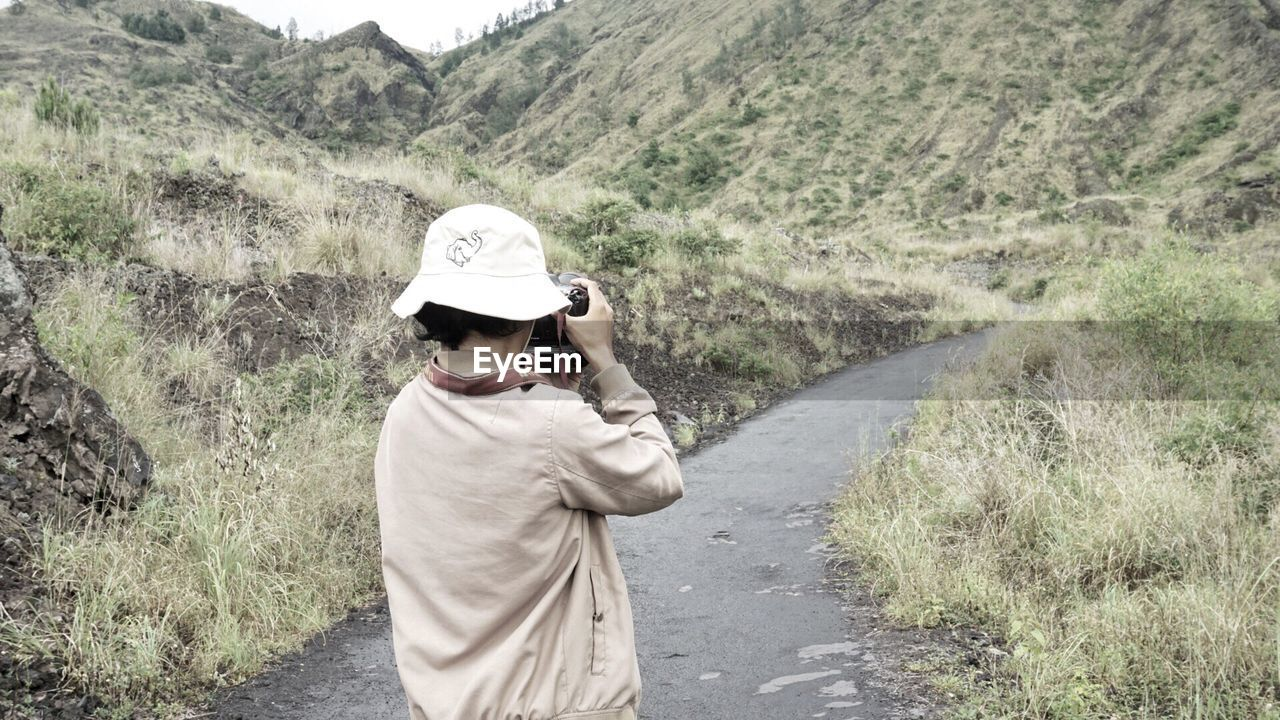 one person, mountain, lifestyles, real people, road, nature, plant, casual clothing, standing, day, leisure activity, men, adult, beauty in nature, transportation, clothing, hat, landscape, scenics - nature, outdoors