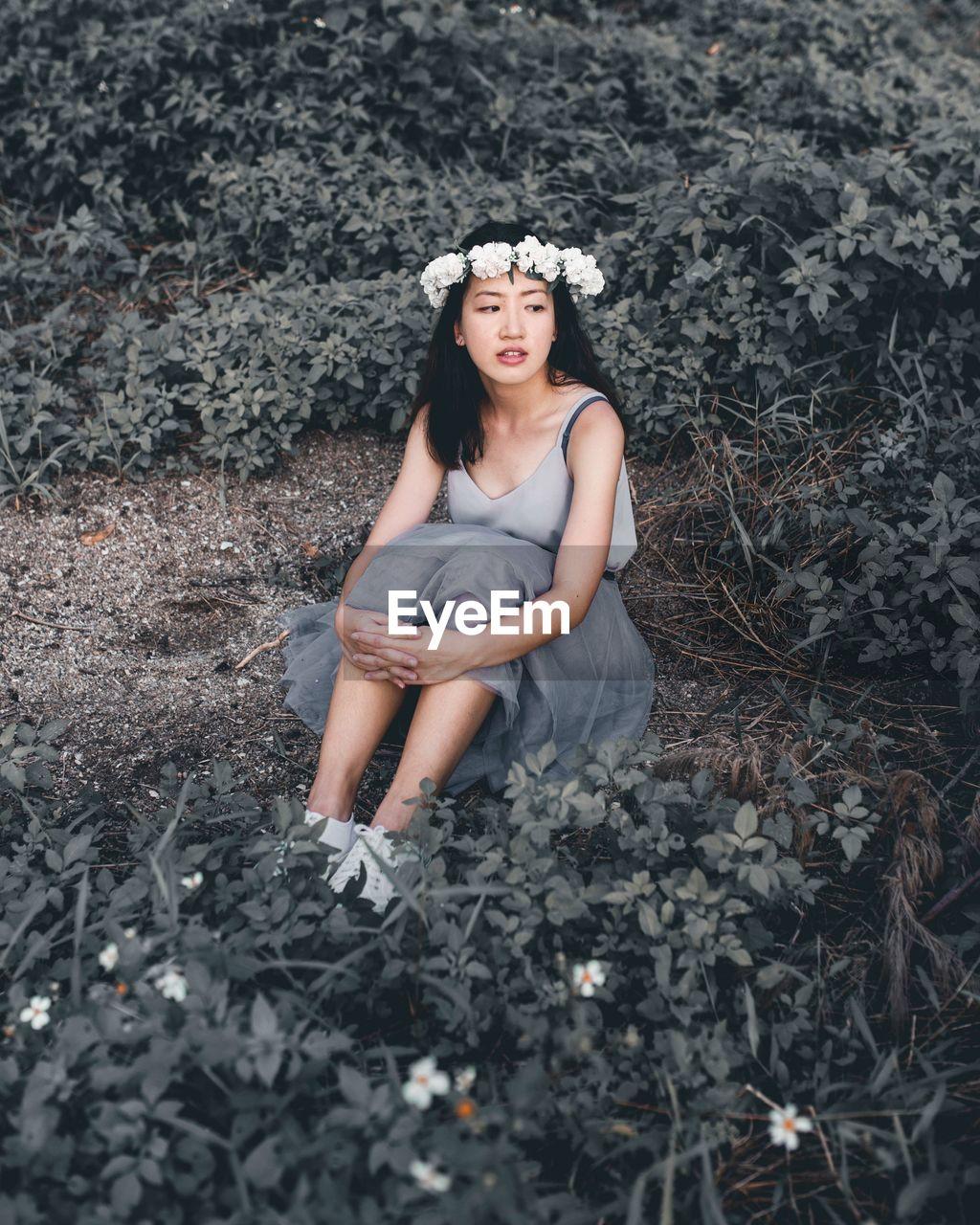 Thoughtful Woman Wearing Flowers Sitting On Field Amidst Plants