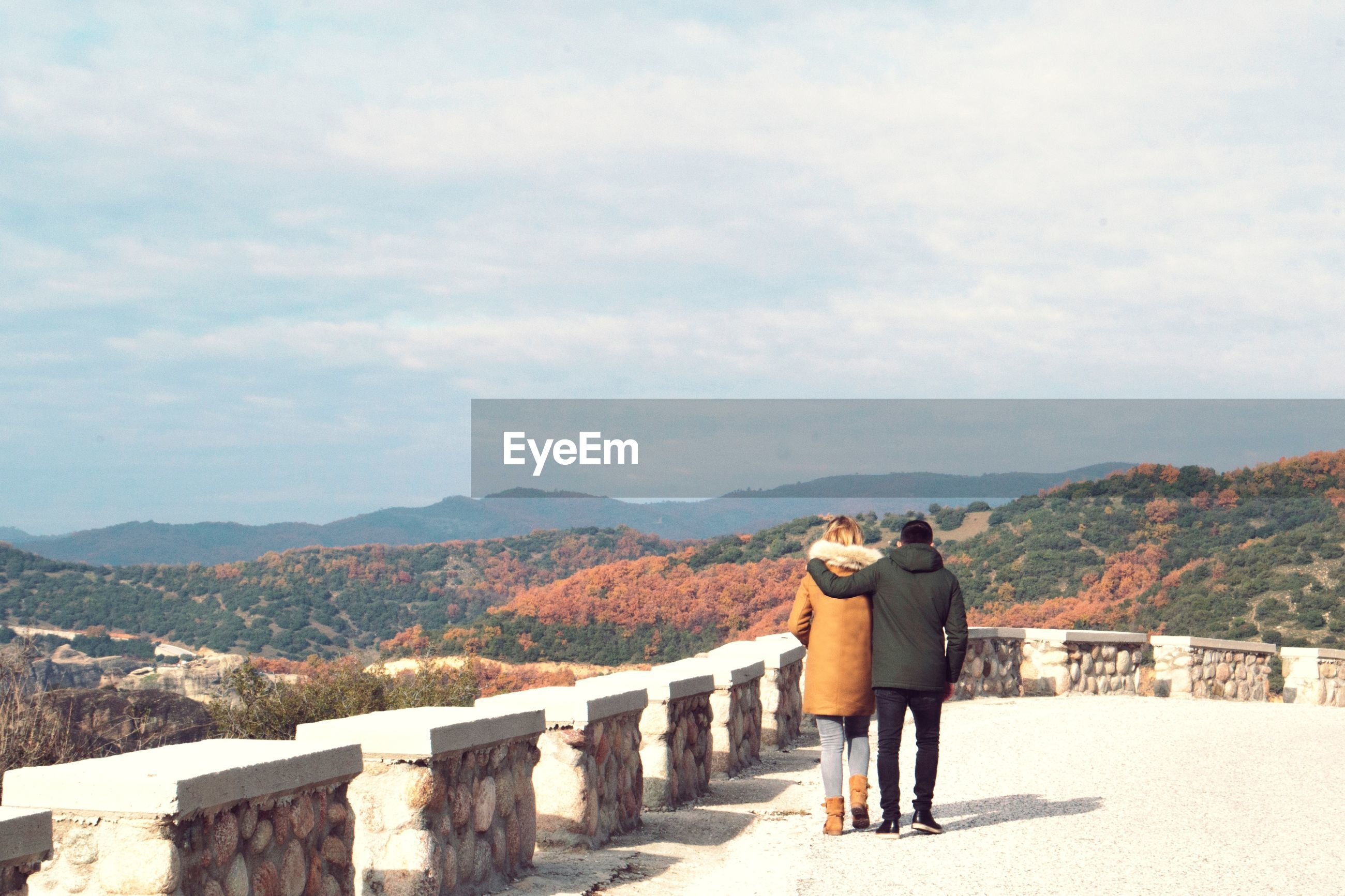 Rear view of couple in warm clothing walking on observation point against sky