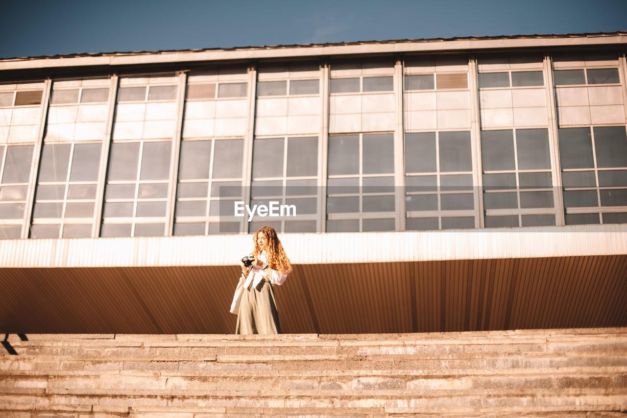 WOMAN LOOKING AWAY AGAINST BUILDING