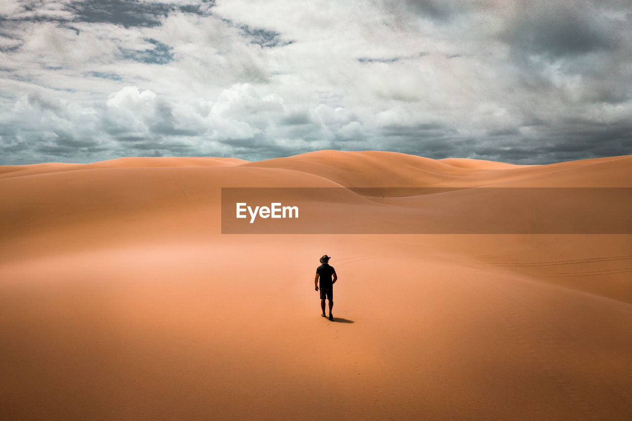 cloud - sky, sky, real people, one person, beauty in nature, scenics - nature, lifestyles, land, sand dune, leisure activity, nature, full length, tranquil scene, non-urban scene, men, sand, landscape, tranquility, standing, climate, arid climate, outdoors