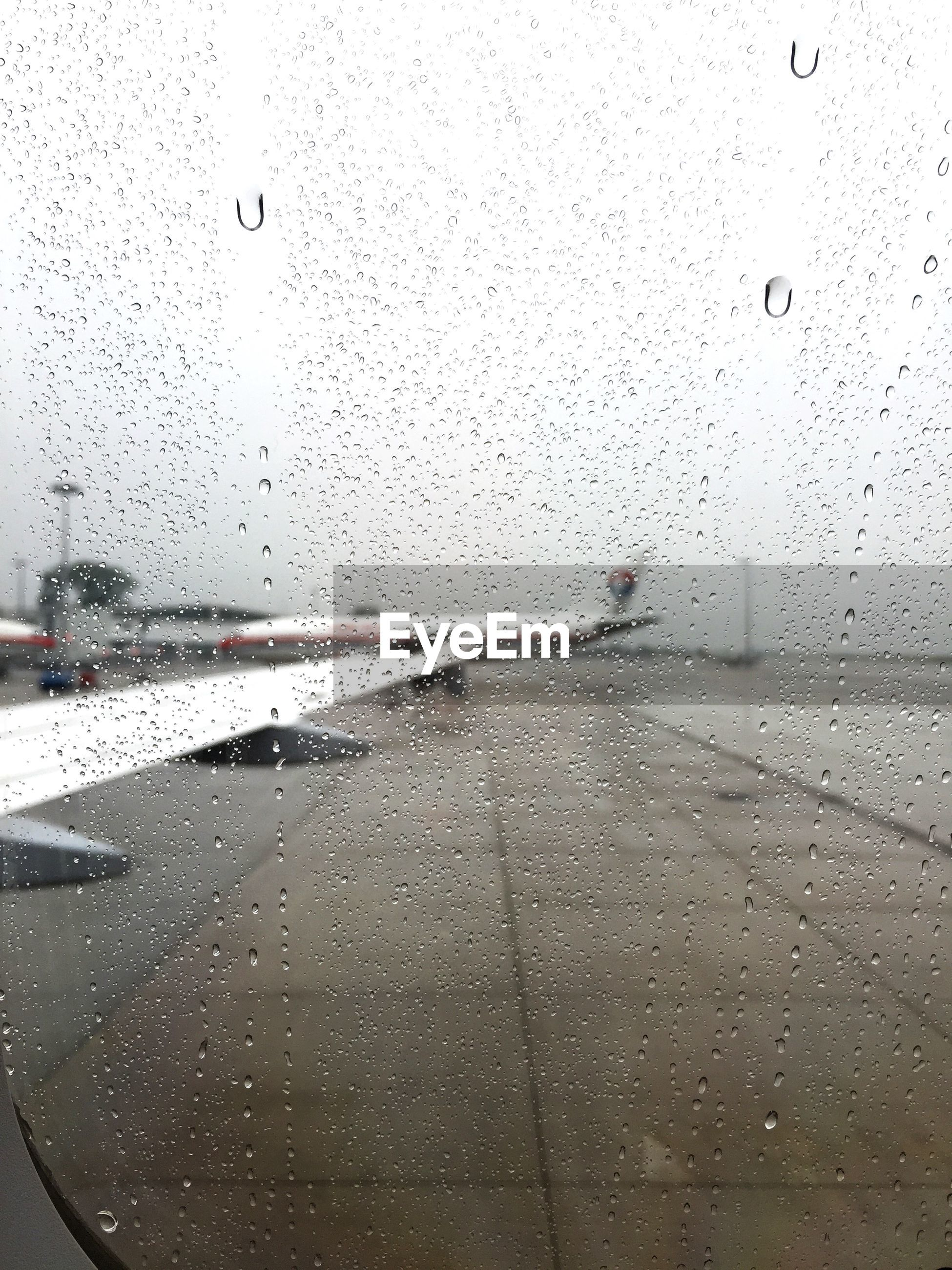 Cropped image of airplane against sky seen through wet window