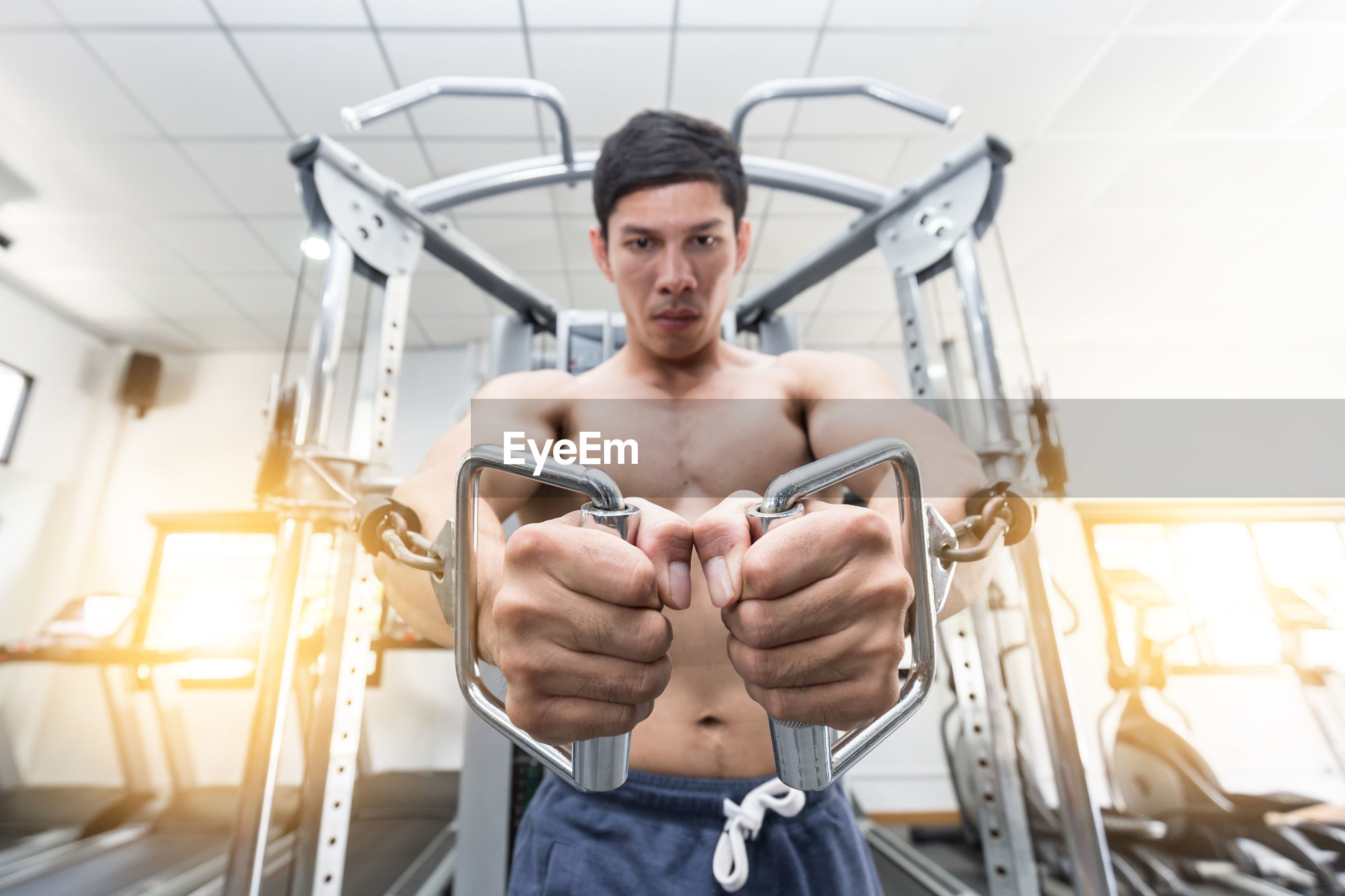 Portrait of shirtless man exercising in gym