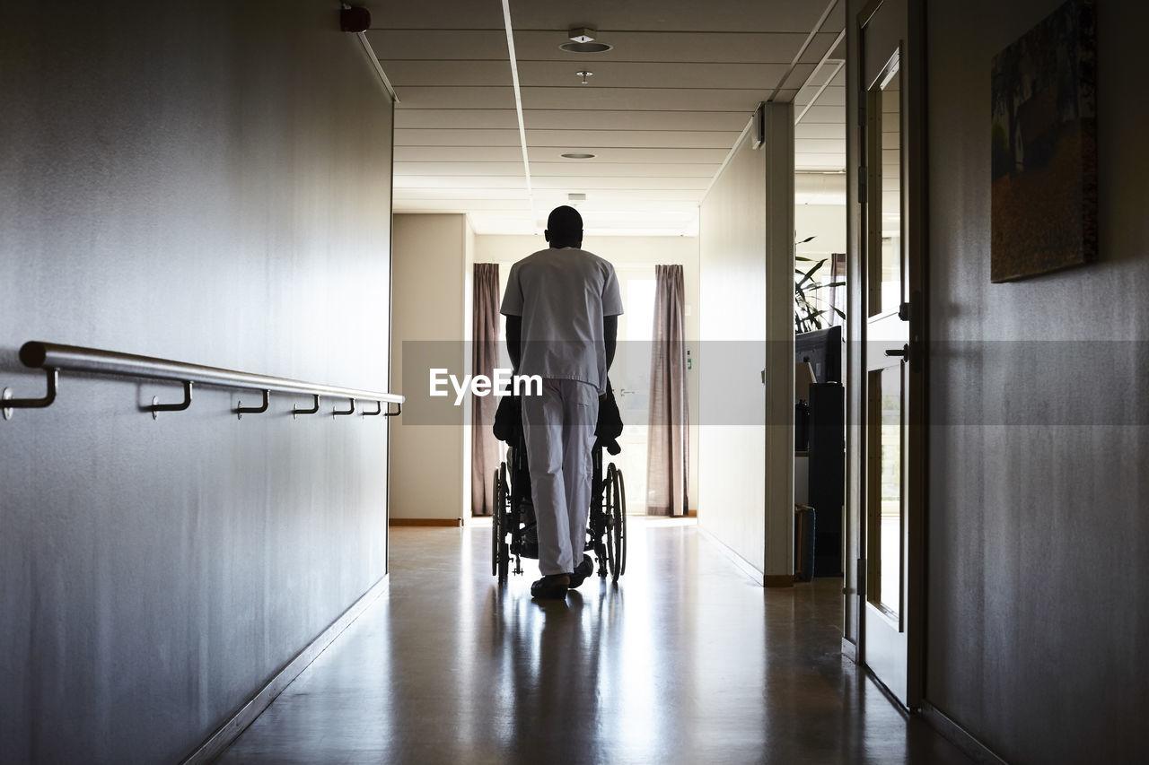 FULL LENGTH REAR VIEW OF MAN WALKING IN BUILDING