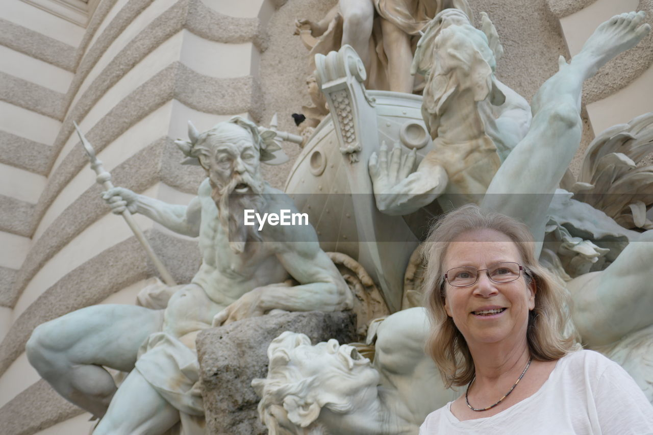 Smiling Woman Standing Against Statues At Hofburg