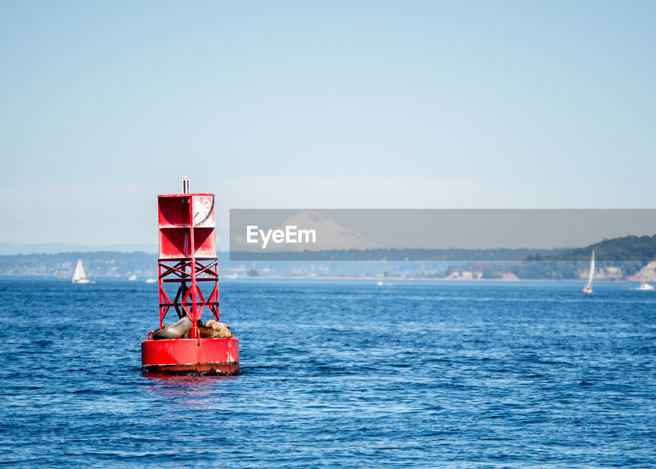 sky, water, sea, day, nature, clear sky, copy space, scenics - nature, waterfront, safety, red, beauty in nature, blue, no people, outdoors, security, non-urban scene, protection, tranquil scene