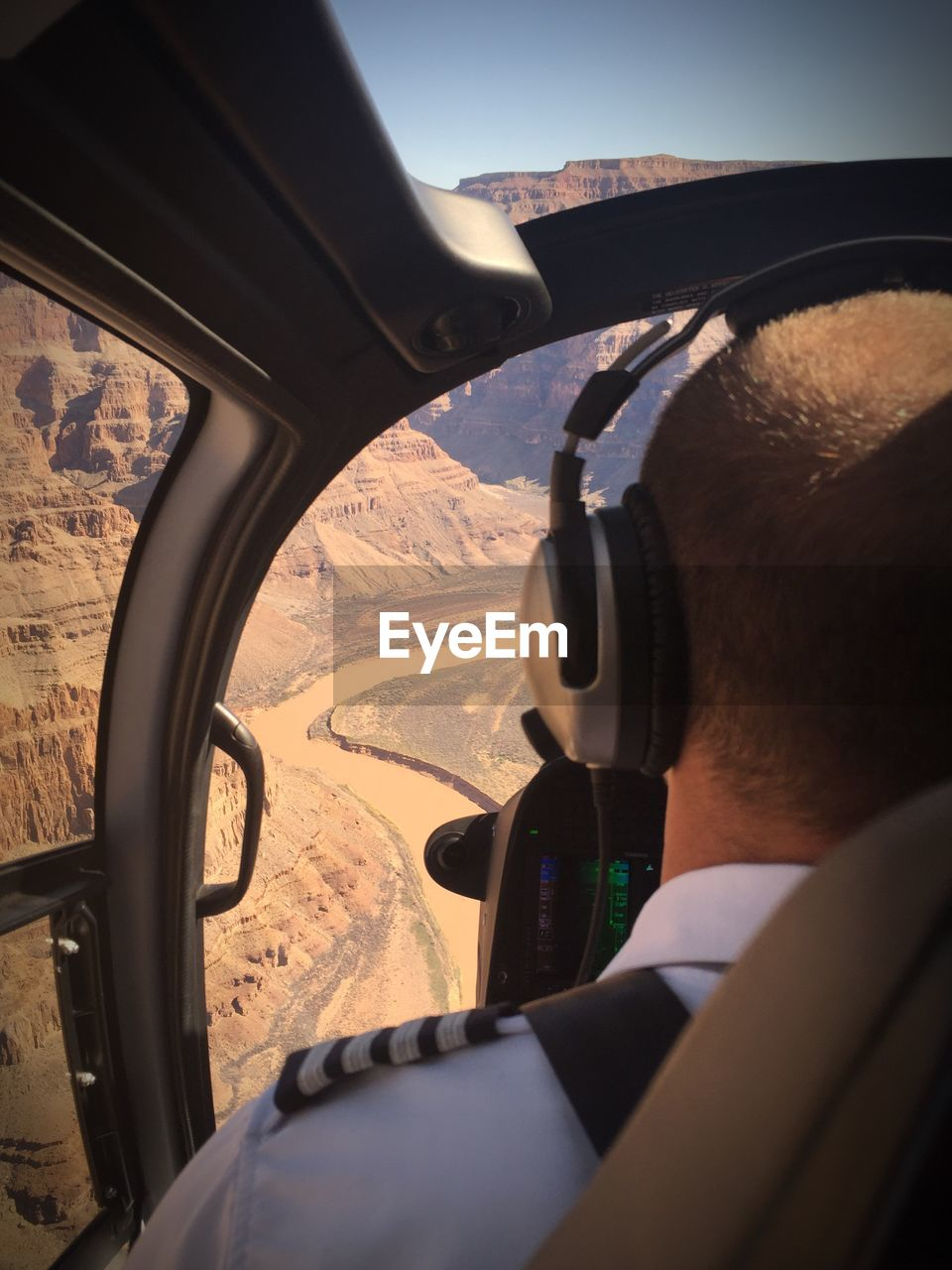 Rear view of man in helicopter on mountain