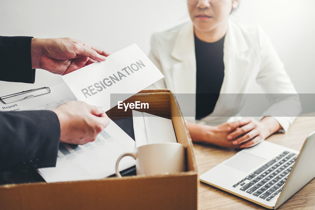 Businessman holding resignation envelope by businesswoman at office