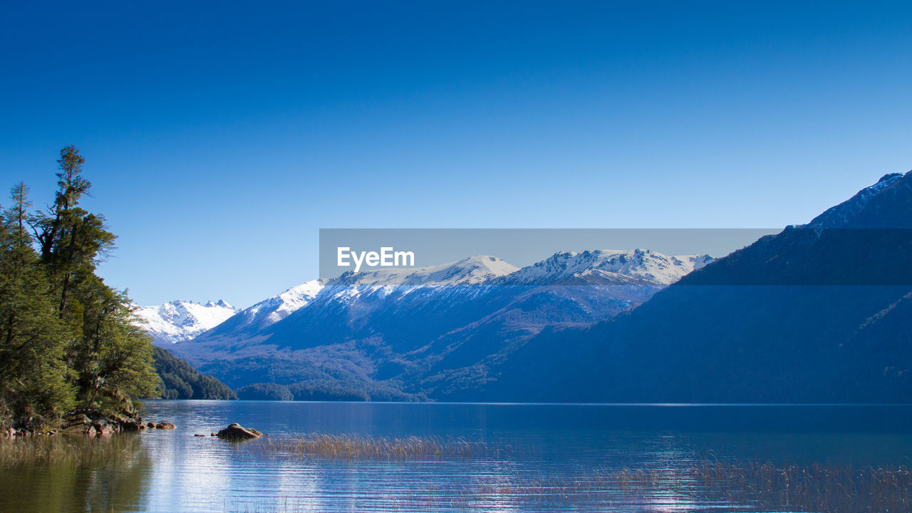 scenics - nature, beauty in nature, mountain, sky, water, tranquil scene, tranquility, cold temperature, blue, winter, lake, waterfront, non-urban scene, nature, idyllic, clear sky, tree, copy space, mountain range, no people, snowcapped mountain