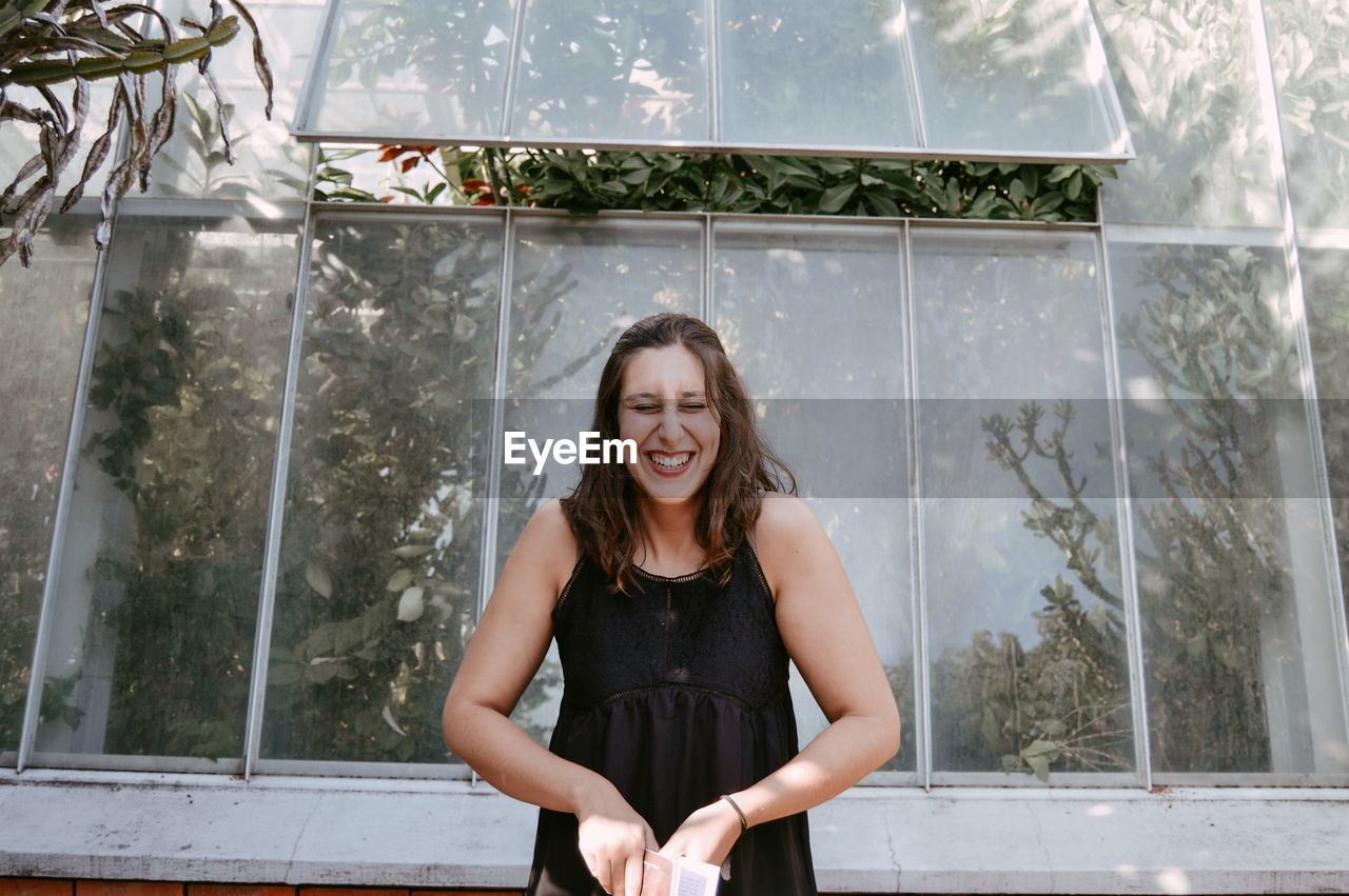 Young Woman Laughing While Standing By Greenhouse