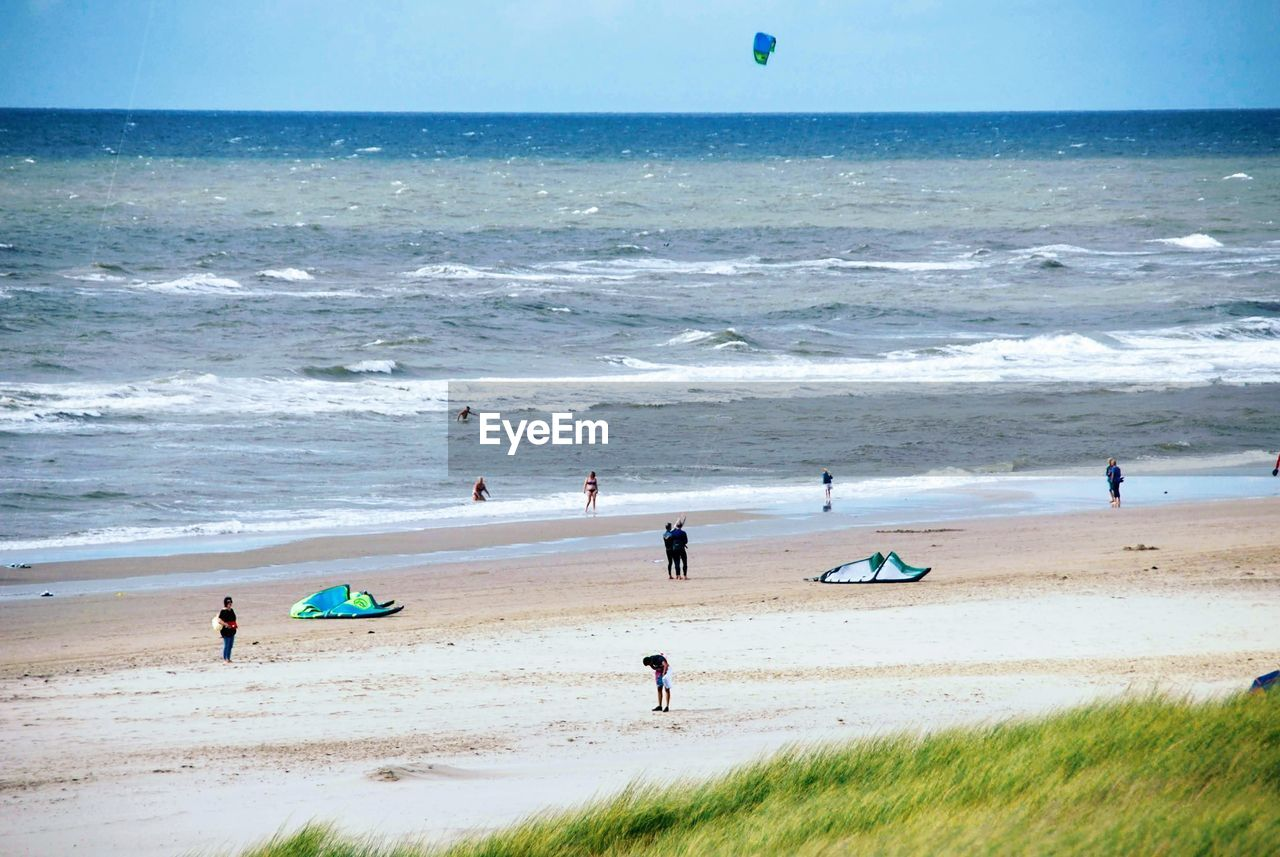 sea, beach, land, water, horizon, horizon over water, sport, sky, beauty in nature, nature, real people, aquatic sport, scenics - nature, leisure activity, motion, lifestyles, group of people, sand, holiday, kiteboarding, outdoors