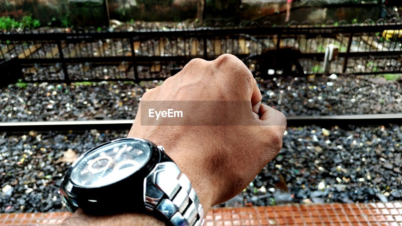 real people, one person, watch, time, men, wristwatch, hand, day, human hand, focus on foreground, track, lifestyles, human body part, rail transportation, railroad track, leisure activity, outdoors, close-up, body part, finger