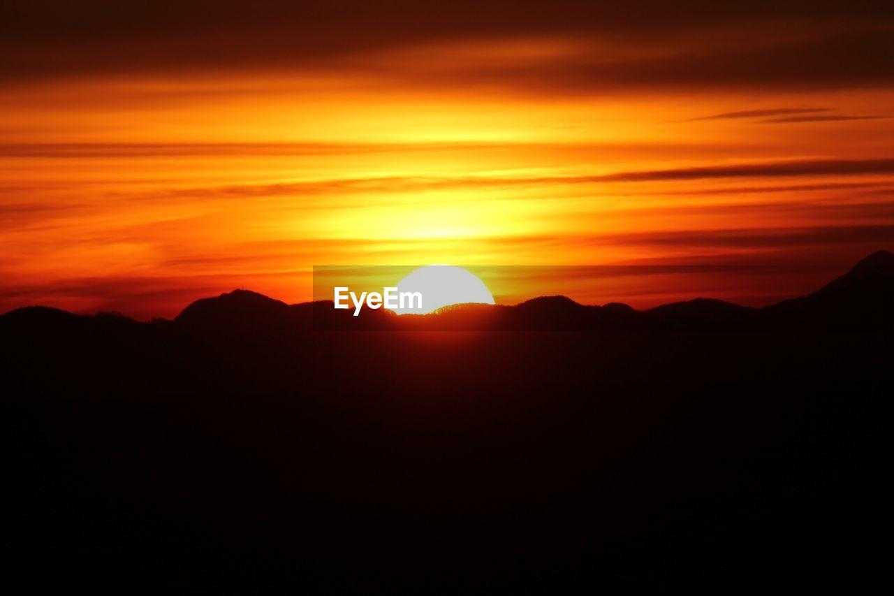 Idyllic shot of mountains against orange sunset sky