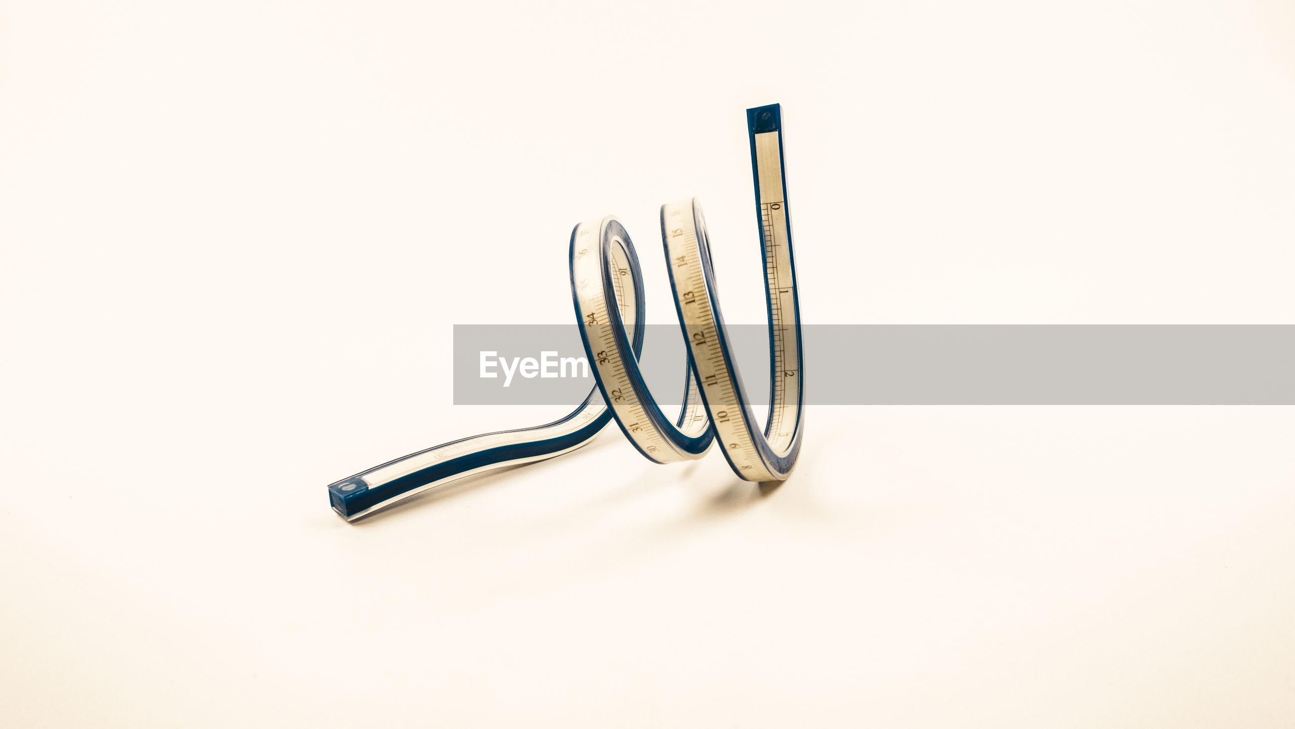 Flat spline vinyl plastic ruler against beige background