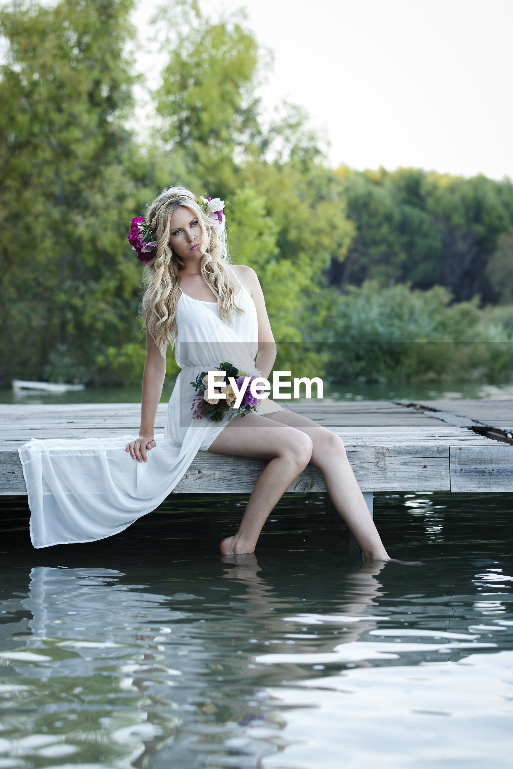 Woman with flowers sitting on jetty over lake against trees