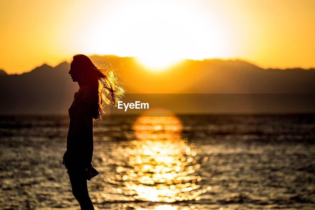 SIDE VIEW OF SILHOUETTE WOMAN STANDING BY SEA AGAINST ORANGE SKY