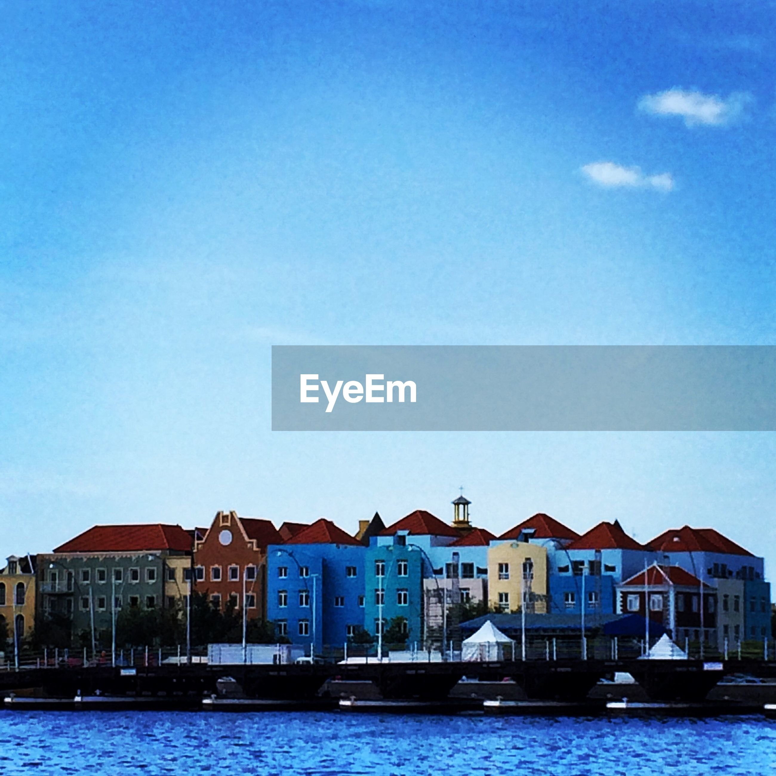 architecture, building exterior, waterfront, built structure, water, blue, residential structure, residential building, clear sky, sky, house, sea, rippled, river, city, day, residential district, nautical vessel, building, outdoors