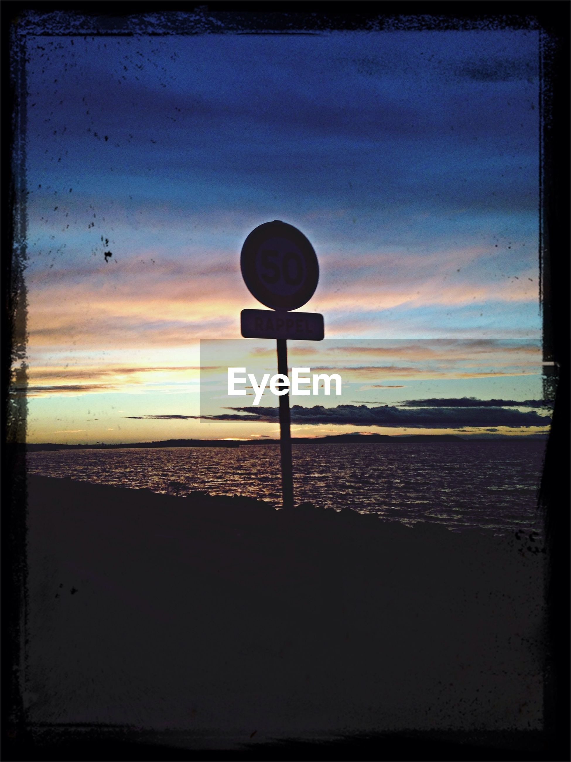 Road sign on street by beach during sunset