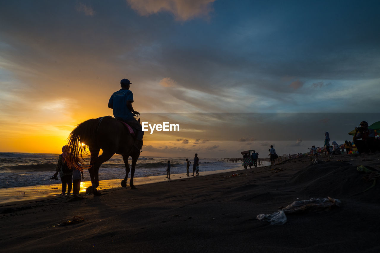 PEOPLE RIDING HORSE AT BEACH AGAINST SKY